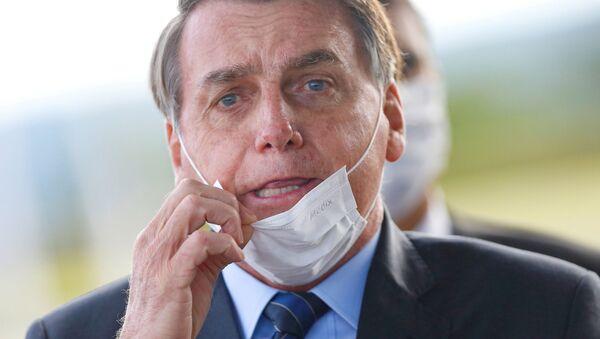 Brazil's President Jair Bolsonaro adjusts his mask as he leaves Alvorada Palace, amid the coronavirus disease (COVID-19) outbreak in Brasilia, Brazil May 13, 2020 - Sputnik International