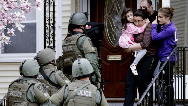 In this April 19, 2013, file photo, a woman carries a girl from their home as a SWAT team searching for a suspect in the Boston Marathon bombings enters the building in Watertown, Mass. - Sputnik International