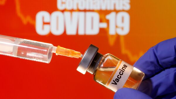 A small bottle labeled with a Vaccine sticker is held near a medical syringe in front of displayed Coronavirus COVID-19 words in this illustration taken April 10, 2020. - Sputnik International
