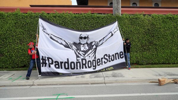 Demonstrators display a banner calling for the pardoning of former Trump presidential campaign advisor Roger Stone, as the presidential motorcade passes through West Palm Beach, Florida - Sputnik International