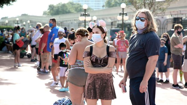 Guests wearing protective masks wait outside the Magic Kingdom theme park at Walt Disney World on the first day of reopening, in Orlando, Florida, on July 11, 2020. - Disney's flagship theme park reopened its doors to the general public on Saturday, along with Animal Kingdom, as part of their phased reopening in the wake of the Covid-19 pandemic. New safety measures have been implemented including mandatory face masks for everyone and temperature checks for guests before they enter. - Sputnik International