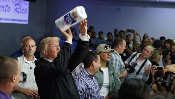 In this Tuesday, Oct. 3, 2017 photo, President Donald Trump tosses paper towels into a crowd at Calvary Chapel in Guaynabo, Puerto Rico - Sputnik International