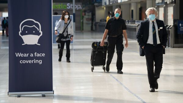 Commuters wearing face masks walk through the concourse at Waterloo Station in London on 15 June 2020 after new rules make wearing face coverings on public transport compulsory while the UK further eases its coronavirus lockdown.  - Sputnik International
