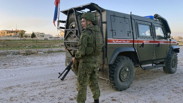 A serviceman of the Russian military police patrols the area near the town of Saraqib, liberated by the Syrian government forces, in Idlib province, Syria - Sputnik International