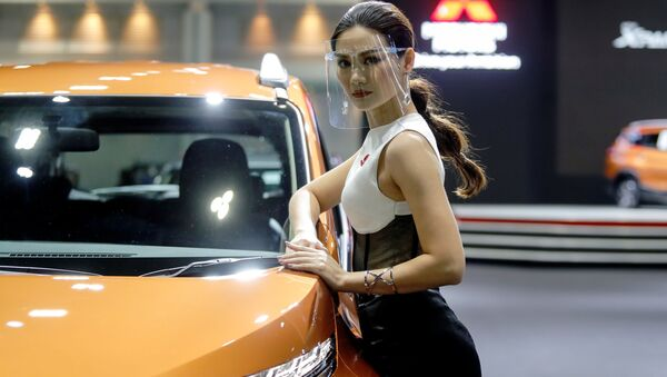 A model wearing a face shield poses with a Mitsubishi vehicle during the media day of the 41st Bangkok International Motor Show after the Thai government eased measures to prevent the spread of the coronavirus disease (COVID-19) in Bangkok, Thailand July 14, 2020.  - Sputnik International