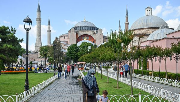 People walk in front of Hagia Sophia on July 11, 2020 in Istanbul, a day after a top Turkish court revoked the sixth-century Hagia Sophia's status as a museum, clearing the way for it to be turned back into a mosque. - Sputnik International