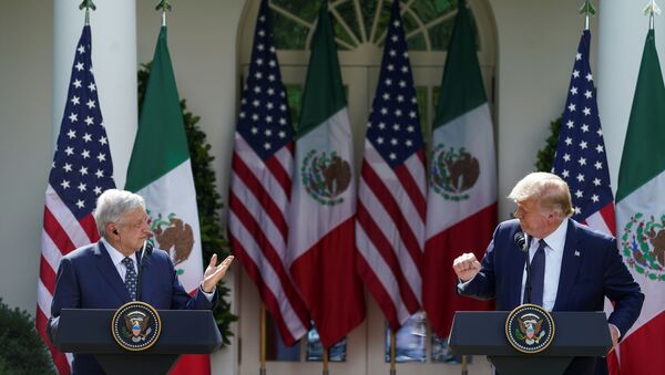 U.S. President Donald Trump listens to Mexico's President Andres Manuel Lopez Obrado as the leaders deliver individual statements prior to signing a joint declaration in the Rose Garden at the White House in Washington, U.S., July 8, 2020 - Sputnik International