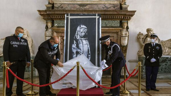 A recovered stolen artwork by British artist Banksy, depicting a young female figure with a mournful expression, that was painted as a tribute to the victims of the 2015 terror attacks at the Bataclan music hall in Paris, is unveiled during a ceremony at the French Embassy in Rome, Tuesday, July 14, 2020, where it was returned by Italian prosecutors to France. The artwork was stolen in 2018 and recovered in June 2020 in Sant'Omero, central Italy by Italian Carabinieri.  - Sputnik International