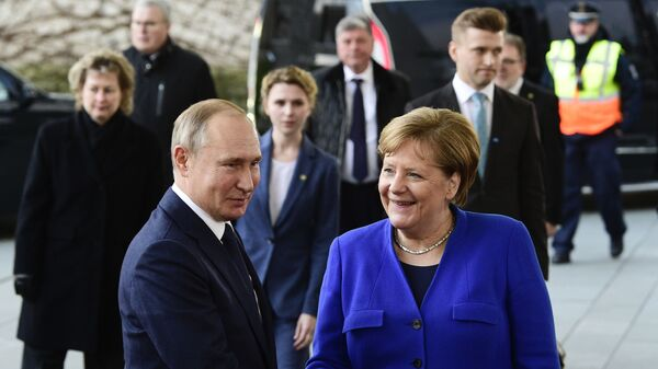 German Chancellor Angela Merkel, right, shakes hands with Russian President Vladimir Putin during arrivals for a conference on Libya at the chancellery in Berlin, Germany, Sunday, Jan. 19, 2020 - Sputnik International