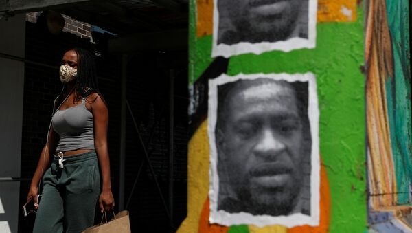 A woman walks with a protective face covering past a mural of George Floyd, in the aftermath of his death in Minneapolis police custody, along 125th street in the Harlem neighborhood of  New York City, New York, U.S., July 9, 2020. - Sputnik International