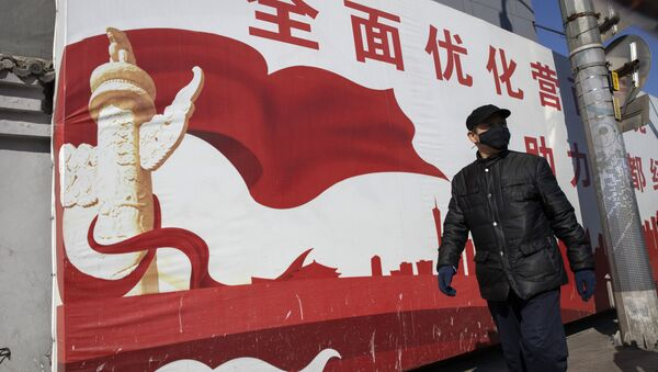 A resident wearing mask walks past government propaganda calling for refinement of the business environment to aid the economic development of the capital in Beijing on Tuesday, March 3, 2020 - Sputnik International