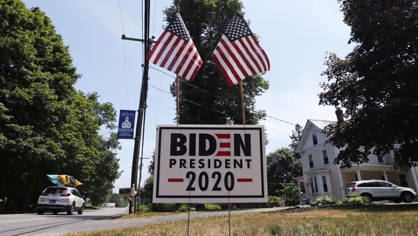 In this 23 June 2020, file photo, a car passes a yard displaying a campaign sign for Democrat presidential candidate, former vice-president Joe Biden in North Hampton, New Hampshire. The coronavirus pandemic isn't going away anytime soon, but campaigns are still forging ahead with in-person organising. The pandemic upended elections this year, forcing campaigns to shift their organising activities almost entirely online and compelling both parties to reconfigure their conventions.  - Sputnik International