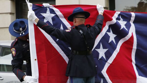 A Mississippi Highway Safety Patrol honor guard folds the retired Mississippi state flag after it was raised over the Capitol grounds one final time in Jackson, Miss., in a July 1, 2020 file photo. - Sputnik International