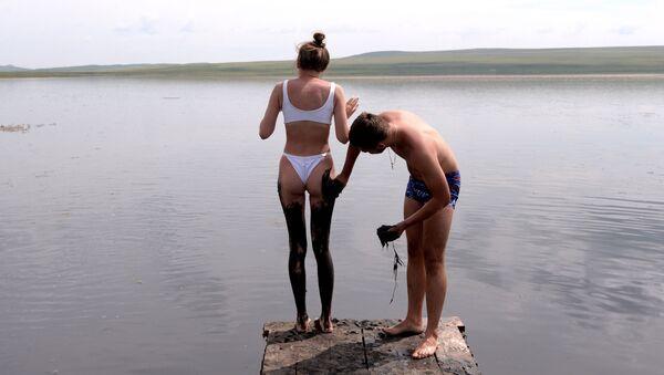 Мужчина намазывает девушку сульфидной грязью из озера Тус в Ширинском районе Республики Хакасия - Sputnik International