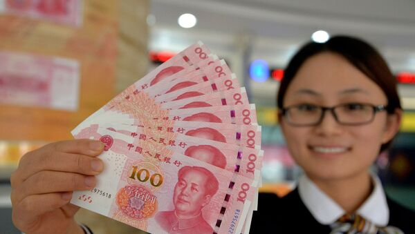 A bank employee shows new 100-yuan banknotes in Handan, north China's Hebei province on 12 November 2015 - Sputnik International