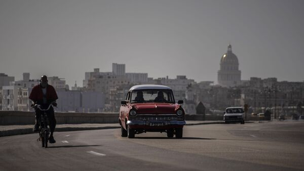 An American classic car and bicycle share the road on the Malecon amid a cloud of Sahara dust in Havana, Cuba, Thursday, June 25, 2020.  - Sputnik International