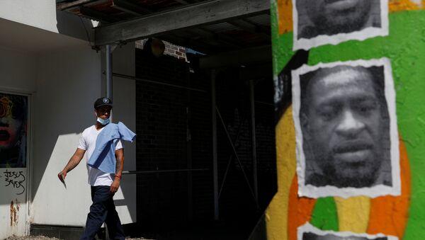 A man walks by a mural of George Floyd, in the aftermath of his death in Minneapolis police custody, along 125th street in the Harlem neighborhood of  New York City, New York, U.S., July 9, 2020. - Sputnik International