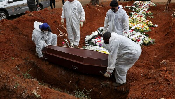 Gravediggers wearing protective suits prepare to bury the coffin containing the body of Elisa Moreira de Araujo, 79, suspected to have died from the coronavirus disease (COVID-19), at Vila Formosa cemetery, in Sao Paulo, Brazil, July 16, 2020. - Sputnik International