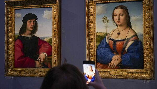 A member of the media takes pictures of 15th century paintings Portraits of Angelo, left, and Maddalena Doni by Raffaello Sanzio da Urbino, during a press tour of the Uffizi museum on the day off its reopening, in Florence, Wednesday, June 3, 2020. The Uffizi museum reopened to the public after over two months of closure due to coronavirus restrictions. - Sputnik International