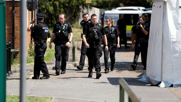 Police officers walk near the block where the suspect of multiple stabbings allegedly lived, in Reading, Britain, 23 June 2020. - Sputnik International