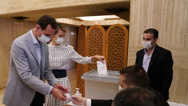 Syria's President Bashar al-Assad and his wife Asma cast their vote inside a polling station during the parliamentary elections in Damascus, Syria in this handout released by SANA on July 19, 2020 - Sputnik International