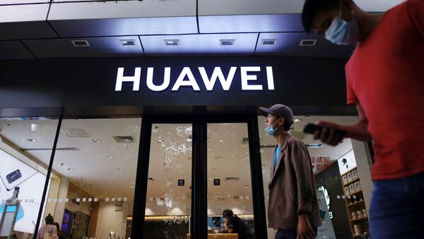 People wearing face masks following the coronavirus disease (COVID-19) outbreak walk past a Huawei store at a shopping mall in Shanghai, China July 14, 2020 - Sputnik International