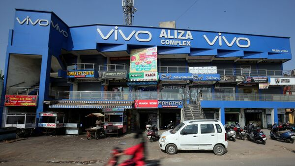 A scooterist rides past a shopping complex with the billboard of Chinese smartphone maker Vivo in Ahmedabad, India, December 14, 2018 - Sputnik International