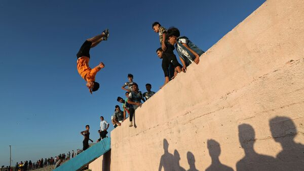 A Palestinian youth demonstrates his parkour skills on a beach as the coronavirus disease (COVID-19) restrictions ease in Gaza City July 10, 2020 - Sputnik International