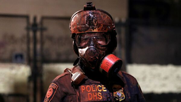 A federal law enforcement officer is covered in red paint during a protest against racial inequality and police violence in Portland, Oregon, U.S., July 26, 2020. - Sputnik International
