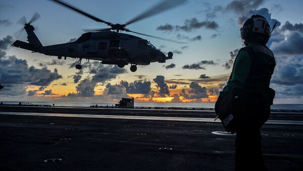 An MH-60R Sea Hawk helicopter launches during flight operations aboard the U.S. Navy aircraft carrier USS Ronald Reagan in the South China Sea July 17, 2020 - Sputnik International