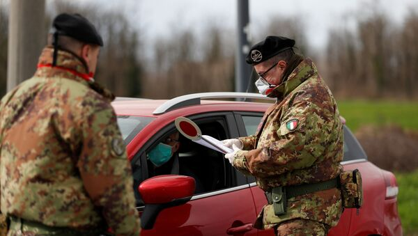 Members of the Italian army wearing protective face masks check the permission of a driver to enter the red zone of Turano Lodigiano, closed off due to a coronavirus outbreak in northern Italy, in Turano Lodigiano, Italy, February 26, 2020. - Sputnik International