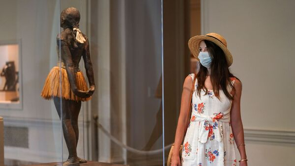 A visitor wearing her face mask looks at the Degas sculpture Little Dancer Aged Fourteen at the National Gallery of Art's West Building, which reopened today after months of  closure due to the coronavirus disease (COVID-19) outbreak, in Washington, U.S., July 20, 2020 - Sputnik International