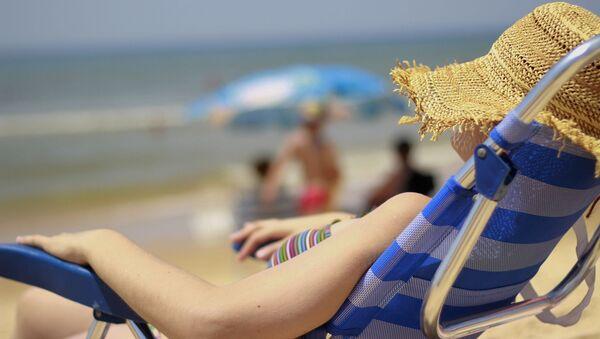 Woman relaxes on the beach in Matalascañas, Spain - Sputnik International