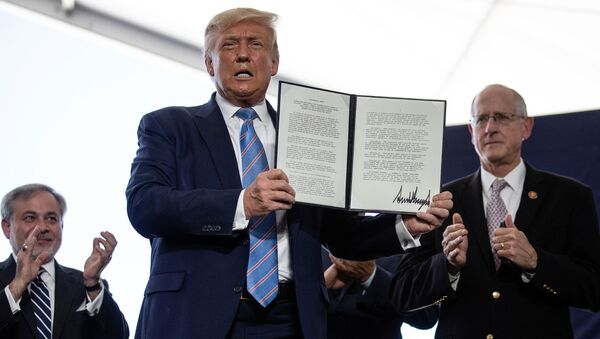 U.S. President Donald Trump is applauded as he displays a presidential permit for energy development that he signed during a tour of the Double Eagle Energy Oil Rig in Midland, Texas, U.S., July 29, 2020. - Sputnik International