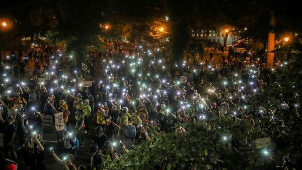 People shine cellphone flashlights during a demonstration against racial inequality and police violence in Portland, Oregon, U.S., July 29, 2020.  - Sputnik International