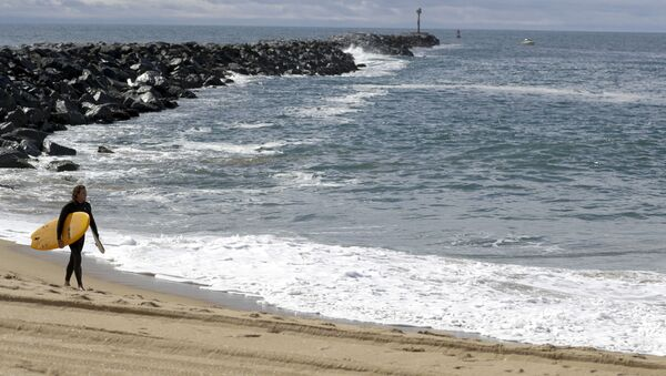 A lone surfer walks along a closed area of the beach in Newport Beach, Calif., Friday, 10 April 2020. The Wedge is closed to all surfboards and flotation devices from 10 a.m. to 5 p.m. May 1 through October 31 each year. - Sputnik International
