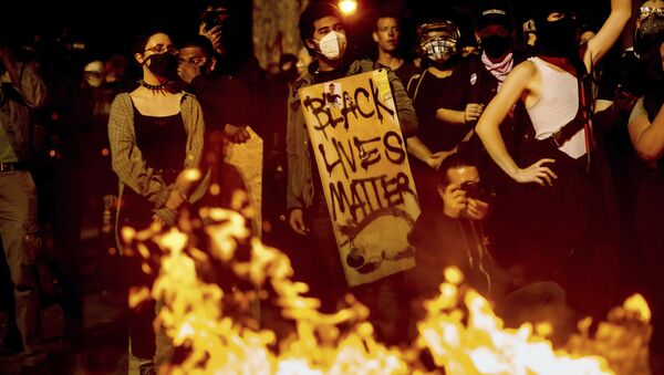 Black Lives Matter protester Jorge Mendoza holds a sign while rallying at the Mark O. Hatfield United States Courthouse on Saturday, Aug. 1, 2020, in Portland, Ore. Following an agreement between Democratic Gov. Kate Brown and the Trump administration to reduce federal officers in the city, nightly protests remained largely peaceful without major confrontations between demonstrators and officers. - Sputnik International