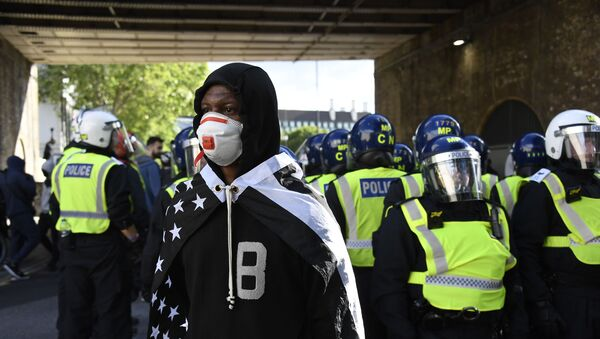 A member of Black Lives Matter movement, draped on a black and white U.S. flag, stands in front of British police officers in riot gear following a protest in central London, Saturday, June 13, 2020. - Sputnik International