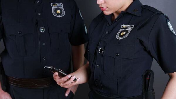 female police officer holding smartphone standing near male police officer - Sputnik International