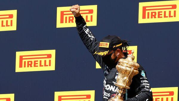 Mercedes' Lewis Hamilton celebrateswinning the race on the podium with the trophy - Sputnik International