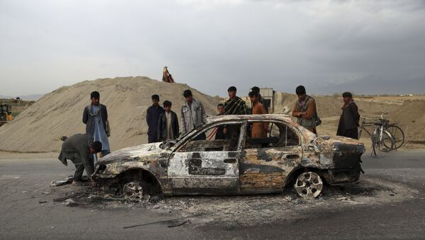 In this April 9, 2019, file photo, Afghans watch a civilian vehicle burnt after being shot by U.S. forces following an attack near the Bagram Air Base, north of Kabul, Afghanistan. Three American service members and a U.S. contractor were killed when their convoy hit a roadside bomb on Monday near the main U.S. base in Afghanistan, the U.S. forces said. The Taliban claimed responsibility for the attack. Intelligence alleging that Afghan militants might have accepted Russian bounties for killing American troops didn't scuttle the U.S.-Taliban agreement or President Donald Trump's plan to withdraw thousands more troops from the war - Sputnik International