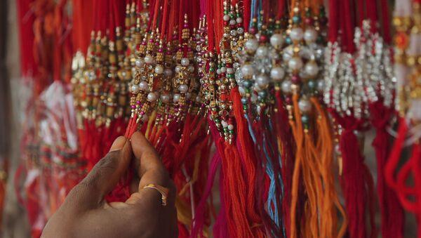 A woman shops for 'rakhi', or a sacred thread, ahead of 'Raksha Bandhan' festival in Hyderabad, India, Friday, July 31, 2020. - Sputnik International