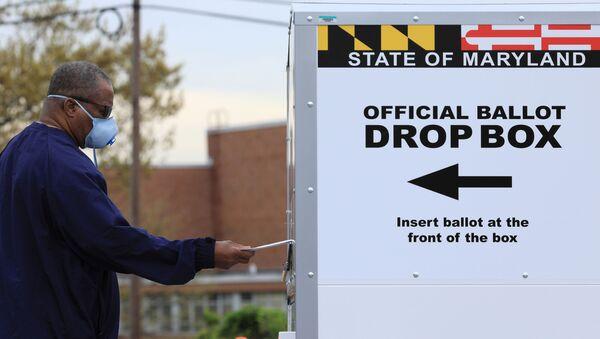 A resident drops off a mail-in ballot at the Edmondson Westside High School Polling site in Baltimore, Maryland, U.S., April 28, 2020 - Sputnik International