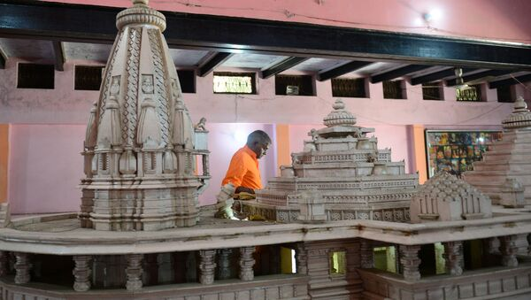A worker walks past a model of a proposed Ram Hindu temple in Ayodhya on November 11, 2019. - Sputnik International