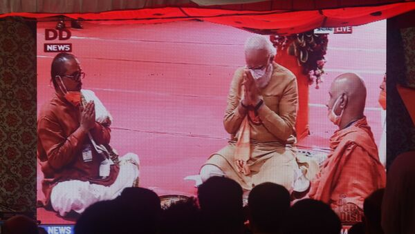 People watch a live telecast on a screen from Ayodhya of India's Prime Minister Narendra Modi taking part in a Hindu religious ritual during a groundbreaking ceremony of the Ram Temple, in New Delhi on August 5, 2020. - Sputnik International