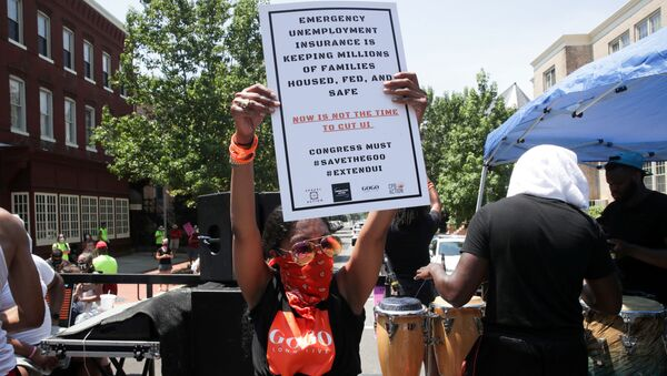 A person holds a placard as protesters temporarily block the street to U.S. Senate Majority Leader Mitch McConnell's (R-KY) house with a live band on a flatbed truck, demanding the extension of coronavirus disease (COVID-19)-related unemployment aid, on Capitol Hill in Washington, U.S. July 22, 2020 - Sputnik International