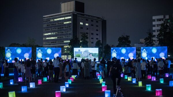 Visitors watch a screen (back C) displaying virtual lanterns as paper lanterns are placed to mark the 75th anniversary of the atomic bombing, at a park in in Hiroshima on August 6, 2020. - Japan on August 6, 2020 marked 75 years since the world's first atomic bomb attack, with the COVID-19 coronavirus pandemic forcing a scaling back of annual ceremonies to commemorate the victims. - Sputnik International
