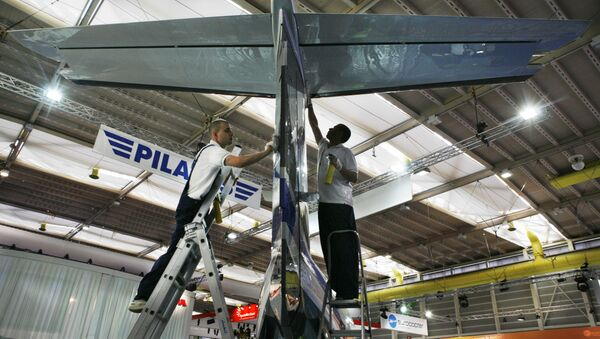 Workers are seen by a Pilatus PC-12 aircraft, during preparations for the upcoming European Business Aviation Convention & Exhibition, EBACE, at the Geneva Palexpo , Geneva, Switzerland,  Monday, May 19, 2008 - Sputnik International