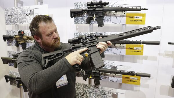 Sergeant Bryan Oberc of Munster, Indiana, US, tries out an AR-15 from Sig Sauer in the exhibition hall at the National Rifle Association's Annual Meeting in state capital, Indianapolis, Saturday, 27 April 2019. - Sputnik International