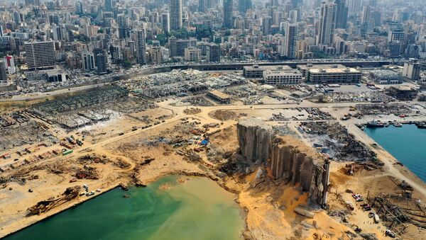 An aerial view taken on August 7, 2020, shows a partial view of the port of Beirut, the damaged grain silo and the crater caused by the colossal explosion three days earlier of a huge pile of ammonium nitrate that had languished for years in a port warehouse, leaving scores of people dead or injured and causing devastation in the Lebanese capital. The city of Beirut can be seen in the background. - Sputnik International